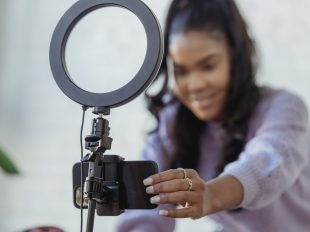 happy-young-woman-setting-up-smartphone-before-shooting-video